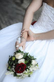 White Caucasian female holding a wedding bouquet. Young woman holding a wedding bouquet at her back in a casual manner. Vertical shot of an elegant bride holding stock image
