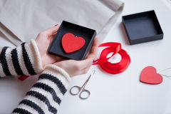 White caucasian hands holding heart shaped toy in box on the won royalty free stock photography