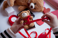 White caucasian hands wrapping teddy bear on the wonderful thing stock photo