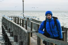 White Caucasian male traveler in a sports blue jacket, gloves, hat, glasses and a backpack standing on the pier of the Atlantic Oc royalty free stock photos