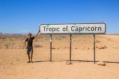 White Caucasian male traveler in sportswear standing next to the Tropic Capricorn sign in Sosusflei National Park stock images