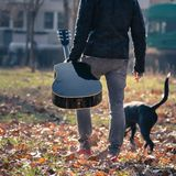 A white Caucasian man with guitar walks a dog in park royalty free stock photo