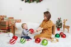 Caucasian mother with baby boy celebrating Christmas or New Year royalty free stock photo