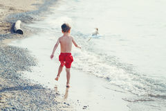 White Caucasian one young little boy in red swim shorts running on beach by water. Funny adorable white Caucasian one young little boy in red swim shorts running Stock Photo
