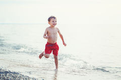 White Caucasian one young little boy in red swim shorts running on beach by water. Portrait of funny adorable white Caucasian one young little boy in red swim Stock Images