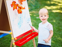 White Caucasian toddler child kid girl standing outside in summer autumn park drawing on easel with markers looking in camera Stock Photo