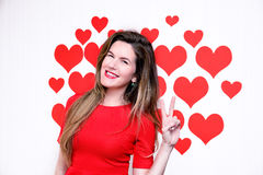 White caucasian woman with red lips giving a counting hand (two sign) on a heart shaped background.Valentine`s Stock Photo