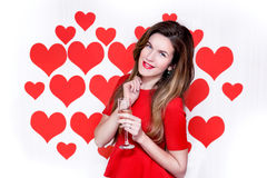 White caucasian woman with red lips holding a champagne glass on heart shaped background.Valentine`s Royalty Free Stock Image