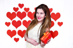 White caucasian woman with red lips holding a gift in one hand on heart shaped background.Valentine day concept Royalty Free Stock Images