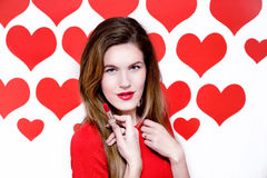 White caucasian woman with red lips holding a red lipstick on heart shaped background.Valentine`s Royalty Free Stock Photography