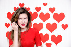 White caucasian woman with red lips standing on a heart shaped background.Valentine`s Stock Images