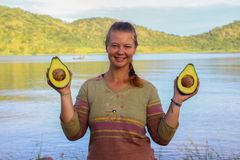 White Caucasian young woman with red hair is smiling and holding two halves of avocado in hand stock images