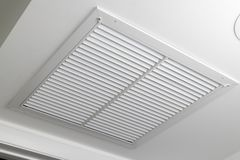 White Ceiling Air Filter Vent Grid. One large white painted metal furnace air vent grill with many openings on a ceiling close-up. Square outflow air filter door stock photos