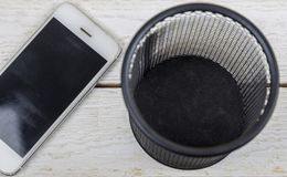 White cell phone near trash can, Electronic waste concept.  stock photography