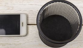 White cell phone near trash can, Electronic waste concept.  royalty free stock photo