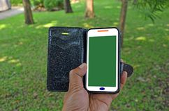 White cellphone with green display in black socket. In hand with grass background Royalty Free Stock Photo