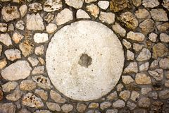 White Cemented Round Shape with Hole in Center. Big Circle Design in Middle of Stone Paved Surface. Dirty Stains and. Smears on Rocks. Design Ideas for Wall royalty free stock photo