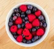 White Ceramic Bowl Full of Bluberries and Red Raspberries. Closeup of a White Ceramic Bowl Full of Bluberries and Red Raspberries Royalty Free Stock Images