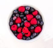 White Ceramic Bowl Full of Bluberries and Red Raspberries on a w. Closeup of a White Ceramic Bowl Full of Bluberries and Red Raspberries on a white background Royalty Free Stock Photography