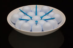 White ceramic bowl full of golf balls. And tees Royalty Free Stock Photos