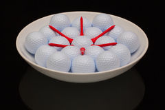 White ceramic bowl full of golf balls. And tees Royalty Free Stock Image