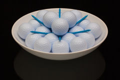White ceramic bowl full of golf balls. And tees Royalty Free Stock Photo