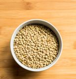 White ceramic bowl of green uncooked lentils. Isolated on white in perspective Royalty Free Stock Images