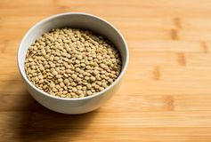 White ceramic bowl of green uncooked lentils. Isolated on white in perspective Stock Images