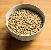 White ceramic bowl of green uncooked lentils. Isolated on white in perspective Royalty Free Stock Photos