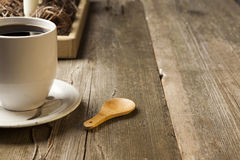 White ceramic coffee cup on rustic table setting. White ceramic coffee cup with wooden spoon on rustic table top Stock Photography