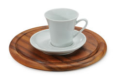 White ceramic coffee cup and white saucer on wooden stand. Stock Photo