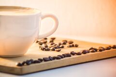 White Ceramic Coffee Mug With Cream Beside Black Coffee Beans Stock Photography