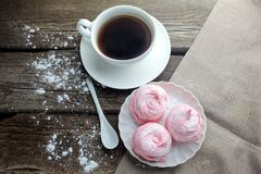 White ceramic cup with black coffee and marshmallow dessert on wooden table, top view. White ceramic cup with black coffee and marshmallow dessert on wooden Royalty Free Stock Photography
