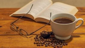 White ceramic cup of black coffee surrounded by small spread of roasted coffee beans, with eye glasses and book atop a wooden coff stock photo