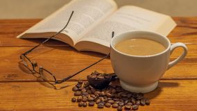 White ceramic cup of coffee with cream, surrounded by small spread of roasted coffee beans, with eye glasses and book atop a woode. N coffee table stock images