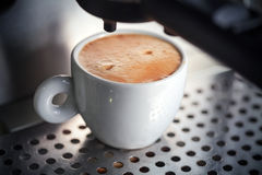 White ceramic cup of fresh espresso with foam. In the coffee machine Stock Photos