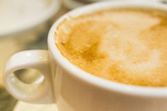White ceramic cup with hot coffee close up. Blurred Royalty Free Stock Photo