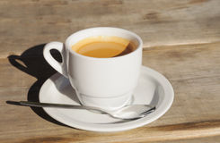 White ceramic cup with hot coffee. On wooden table outdoors Royalty Free Stock Photo