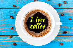 White ceramic cup with I LOVE COFFEE text. Standing on a rustic kitchen table with coffee beans. Top view Stock Photos