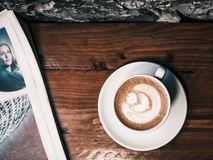 White Ceramic Cup of Latte Beside White Newspaper Royalty Free Stock Images
