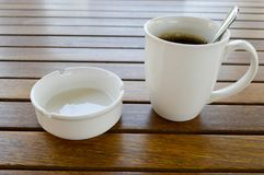 A white ceramic cup with a morning refreshing hot coffee with tea drink and tea shiny teaspoon and an empty cigarette ashtray stock images