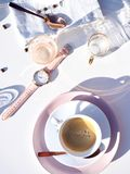 White Ceramic Cup on Saucer Near Gold-colored Analog Watch on Table stock photo