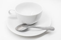 A white ceramic cup with saucer and silver teaspoon isolated on Royalty Free Stock Photography