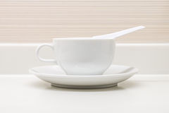 A white ceramic cup with saucer and soup spoon Royalty Free Stock Images