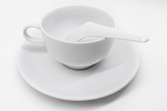 A white ceramic cup with saucer and soup spoon Stock Image