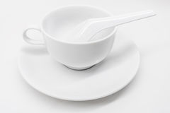 A white ceramic cup with saucer and soup spoon Stock Images