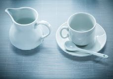 White ceramic cup saucer teaspoon creamer on striped background.  Stock Images