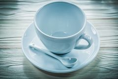 White ceramic cup saucer teaspoon on wooden board.  Stock Photo