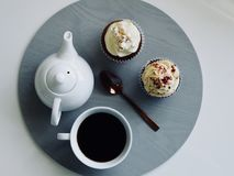 White Ceramic Cup and Teapot with Cupcakes Royalty Free Stock Images