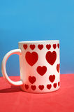 White ceramic cup whit red hearts Stock Photos